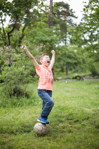 Excited boy shouting with arms raised while standing on soccer ball at back yardの写真素材 [FYI02146305]