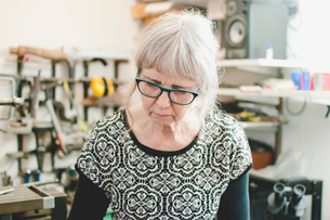 Senior woman wearing glasses while working in jewelry workshopの写真素材 [FYI02146315]