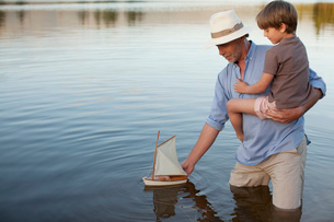 Grandfather and grandson wading in lake with toy sailboatの写真素材 [FYI02146331]