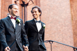 Low angle view of happy gay couple walking while holding handsの写真素材 [FYI02146351]