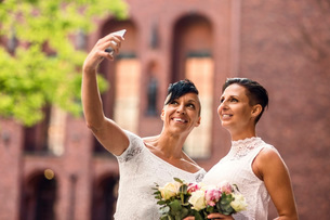 Happy lesbian couple taking selfie from mobile phoneの写真素材 [FYI02146384]