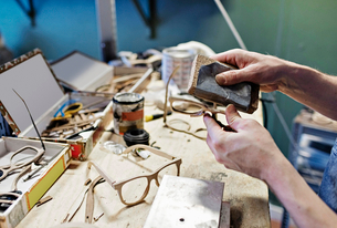 Cropped image of male owner rubbing eyeglasses with work tool at workshopの写真素材 [FYI02146385]