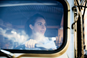 Young saleswoman looking away while driving food truckの写真素材 [FYI02146463]