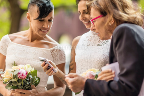 Lesbian couple with priest looking at mobile phoneの写真素材 [FYI02146516]