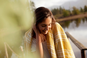 Smiling woman wrapped in blanket at lakesideの写真素材 [FYI02146523]