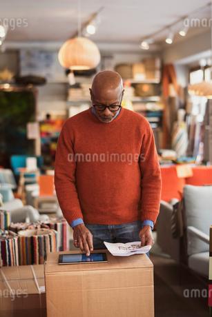 Senior man using digital tablet on box at storeの写真素材 [FYI02146531]