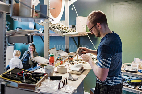 Male owner working at desk in eyewear workshop while family sitting in backgroundの写真素材 [FYI02146535]