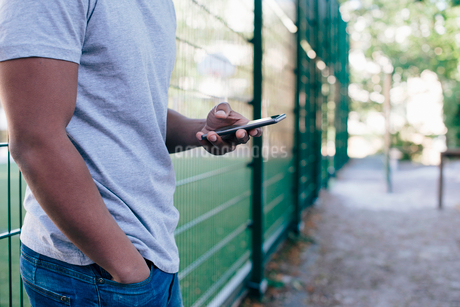 Midsection of young man standing against fence while using smart phoneの写真素材 [FYI02146554]