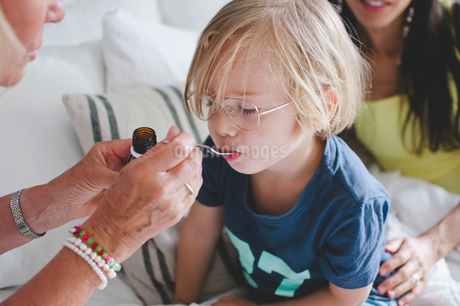 Grandmother feeding medicine to boy with woman sitting in backgroundの写真素材 [FYI02146561]