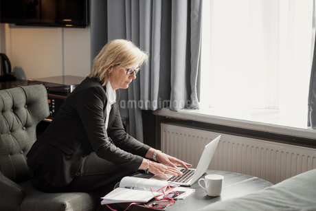 Side view of businesswoman using laptop by window at hotel roomの写真素材 [FYI02146567]