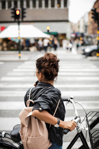 Woman with bicycle standing on zebra crossing in cityの写真素材 [FYI02146573]