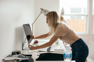 Side view of female graphic designer touching desktop monitor at homeの写真素材 [FYI02146578]