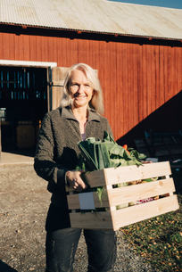 Portrait of smiling mature woman carrying crate full of vegetables with barn in backgroundの写真素材 [FYI02146594]