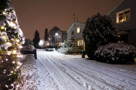 Houses by snow covered road during Christmas at nightの写真素材 [FYI02146609]