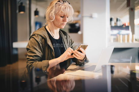 Businesswoman using smart phone while sitting at desk in officeの写真素材 [FYI02146626]