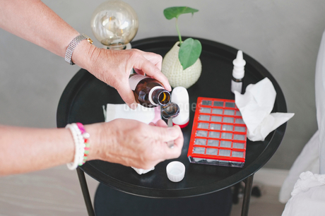Cropped image of senior woman pouring medicine in spoon by table at homeの写真素材 [FYI02146655]