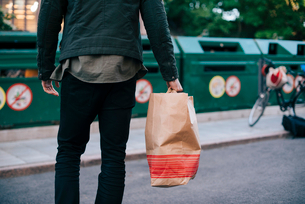 Midsection of man carrying paper bag against garbage cansの写真素材 [FYI02146670]