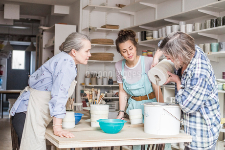 Senior potter and young employee looking at mature colleague pouring clay from vase in strainer on bの写真素材 [FYI02146678]