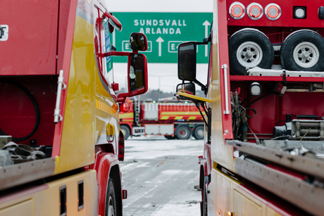 Red and yellow tow trucks on road during winterの写真素材 [FYI02146704]