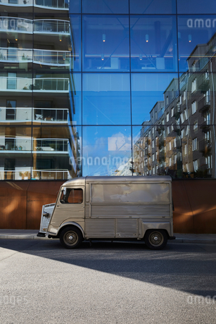 Food truck parked on city street against modern glass buildingの写真素材 [FYI02146708]