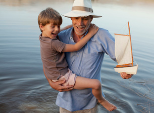 Smiling grandfather and grandson with toy sailboat wading inの写真素材 [FYI02146754]