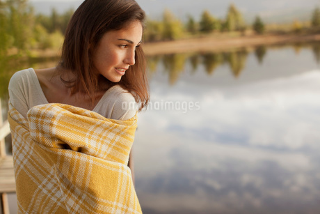 Smiling woman wrapped in blanket at lakesideの写真素材 [FYI02146762]
