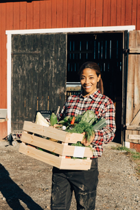 Portrait of smiling mature woman carrying crate full of vegetables with barn in backgroundの写真素材 [FYI02146784]