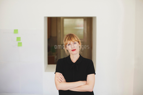 Portrait of confident mid adult businesswoman standing arms crossed in officeの写真素材 [FYI02146786]