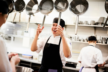Male chef holding colanders while talking with colleague in commercial kitchenの写真素材 [FYI02146827]