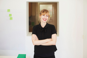Portrait of smiling mid adult businesswoman standing arms crossed in officeの写真素材 [FYI02146852]
