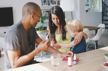 Parents giving medicine to son while sitting at tableの写真素材 [FYI02146869]