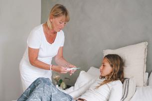Grandmother examining granddaughter's temperature in bedroomの写真素材 [FYI02146874]