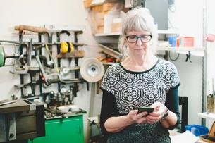 Senior woman using mobile phone in jewelry workshopの写真素材 [FYI02146893]