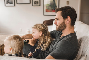 Mid adult father with daughters watching TV in living room at homeの写真素材 [FYI02146905]