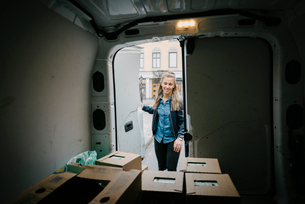 Smiling female worker closing door of delivery vanの写真素材 [FYI02146912]