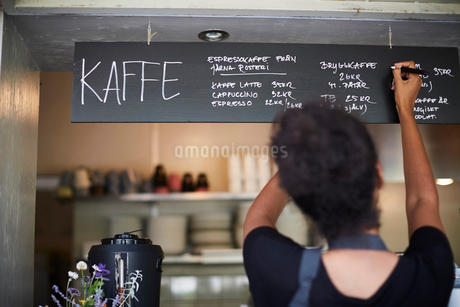 Rear view of waitress writing on blackboard at cafeの写真素材 [FYI02146975]