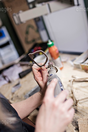 Cropped image of female owner making eyeglasses with work tool at workshopの写真素材 [FYI02146990]
