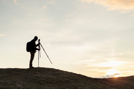 Side view of silhouette hiker fixing tripod on hill against sky during sunsetの写真素材 [FYI02147083]