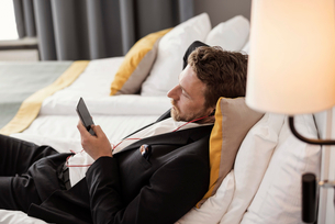 High angle view of businessman using mobile phone listening to music while lying on bed at hotel rooの写真素材 [FYI02147114]