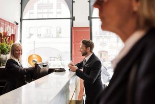 Happy businessman talking to female receptionist at hotel receptionの写真素材 [FYI02147130]