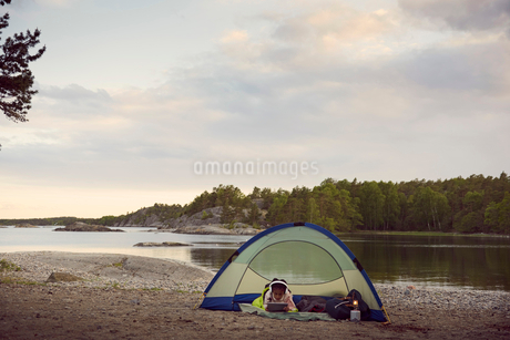 Girl using digital tablet while lying in tent at beach against sky during sunsetの写真素材 [FYI02147136]