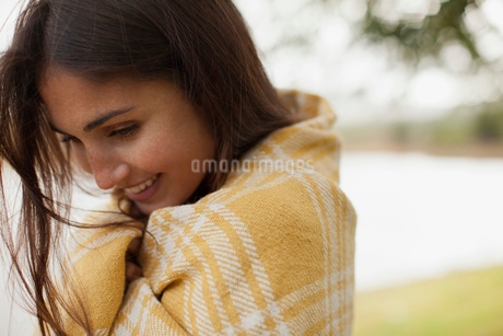 Close up of smiling woman wrapped in blanket at lakesideの写真素材 [FYI02147143]
