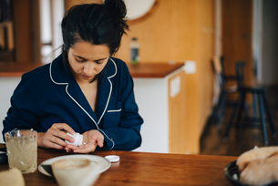 Woman taking medicine during breakfast while sitting at tableの写真素材 [FYI02147156]