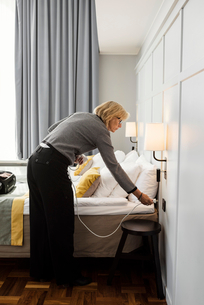 Businesswoman plugging cable by bed at hotel roomの写真素材 [FYI02147182]