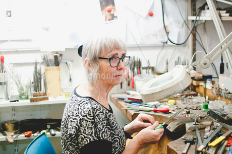Senior craftsperson looking away while making jewelry in workshopの写真素材 [FYI02147197]