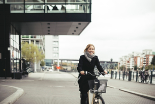 Smiling mid adult businesswoman riding bicycle on city streetの写真素材 [FYI02147223]