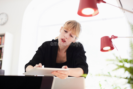 Mid adult businesswoman using digital table in officeの写真素材 [FYI02147263]