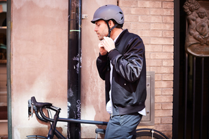 Side view of businessman wearing helmet while sitting on bicycle by wall at cityの写真素材 [FYI02147268]