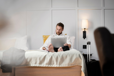 Businessman sitting on bed using laptop against wall in hotel roomの写真素材 [FYI02147274]