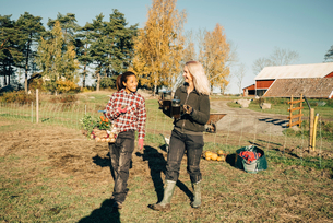 Smiling female farmers with vegetables and French press walking on fieldの写真素材 [FYI02147290]